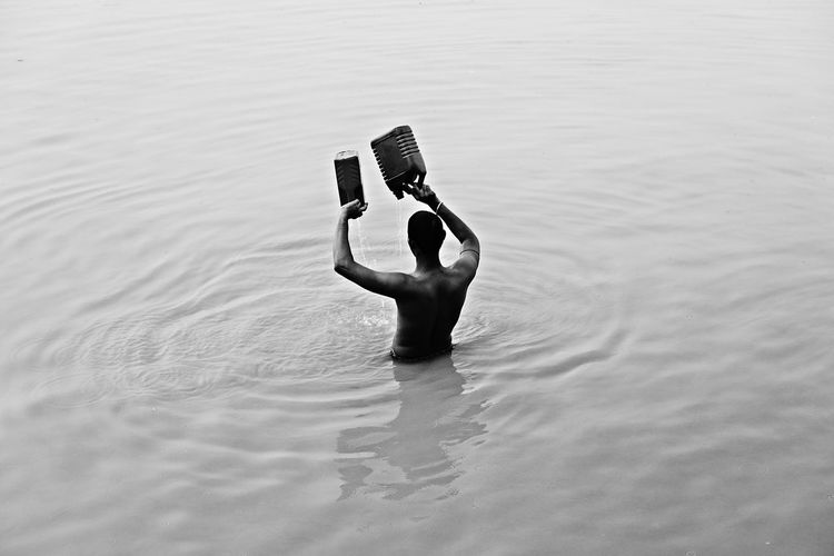 Rear view of man holding can while standing in ganges river