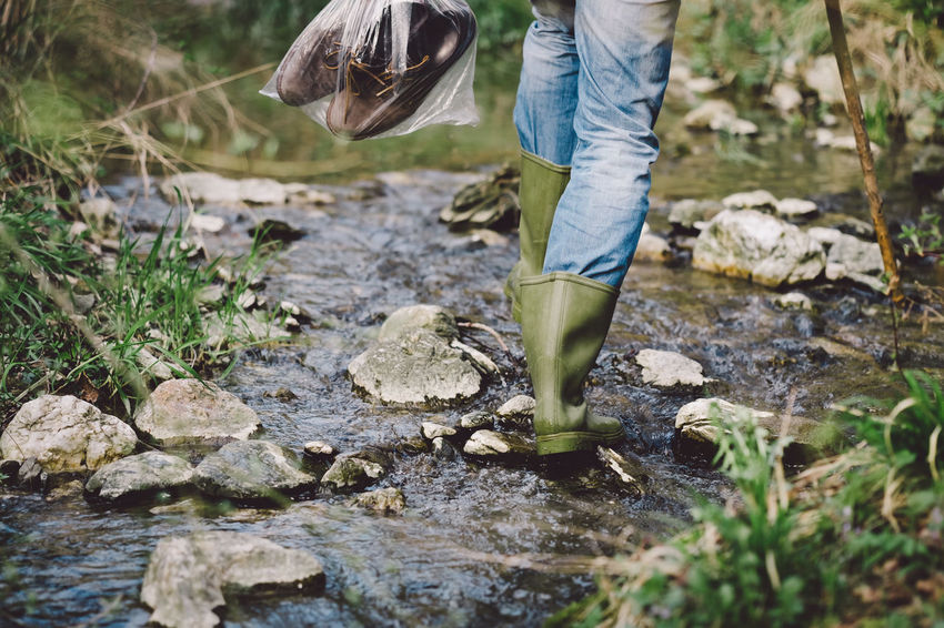 Adult Body Part Casual Clothing Day Flowing Human Body Part Human Leg Jeans Low Section Motion Nature One Person Outdoors Plant Rock Rock - Object Selective Focus Shoe Solid Stream - Flowing Water Water