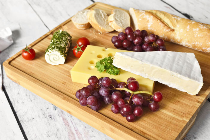 Gourmet cheese plate with bamboo cutting board, fresh cheese variation and wine grapes on a wooden table. Baguette Cheese! Wooden Table Brie Camenbert Cheese Cheese Plate Choice Close-up Cutting Board Dairy Product Food Food And Drink Freshness Fruit Grapes Healthy Eating Indoors  No People Still Life Table Tomatoes Variation Wine Grapes Wood - Material