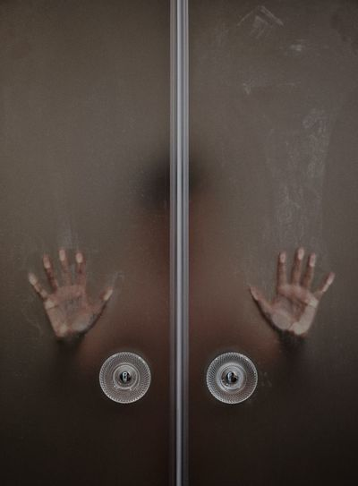 Person In Bathroom Seen Through Glass Door