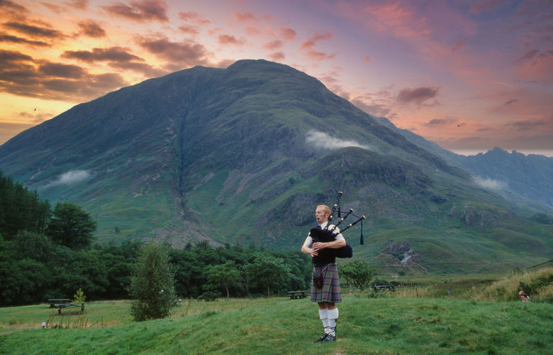 Full length of bagpiper standing on field against mountain