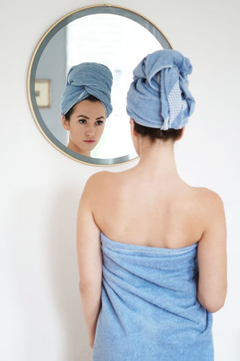 Reflection Of Woman On Mirror In Bathroom At Home