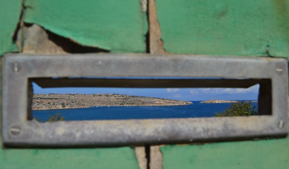 Close up shot with Nikon D3100 through a letterbox in a weathered green doorway with St. Paul's Bay in the background. Blue Close-up Day Green Green Color Letterbox Malta No People Old Doors, Weathered White, Weathered Brown Edge, Antique Doors Peeling Paint Seascape Slot St Paul's Bay Weathered
