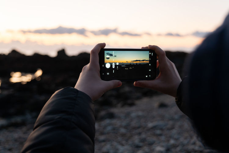 Midsection of man photographing with mobile phone at sunset