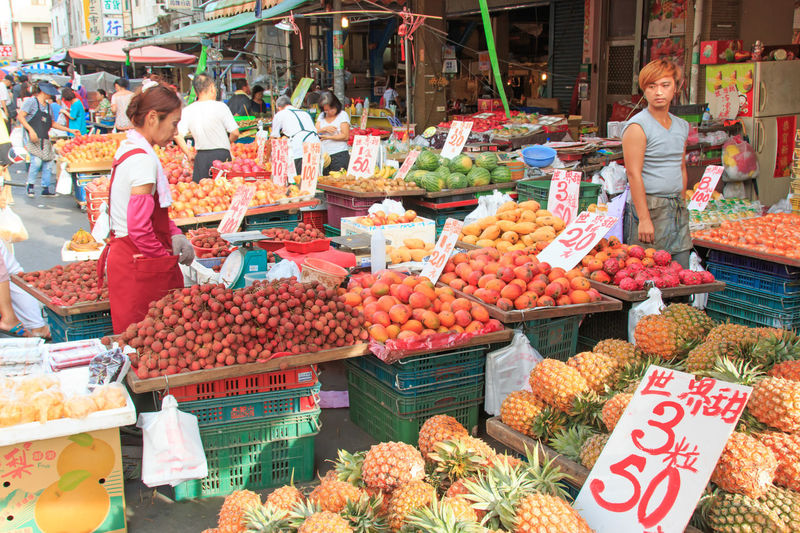 Kaohsiung, Taiwan - June 22,2015: People selling and buying food in a traditional fruit and vegetable market of Taiwan Abundance Arrangement Choice Display Food For Sale Freshness Fruit Large Group Of Objects Market Market Market Stall Price Tag Retail  Sale Shop Shopping Small Business Store Street Market Taiwan Taiwan Food Taiwanese Variation Vegetables