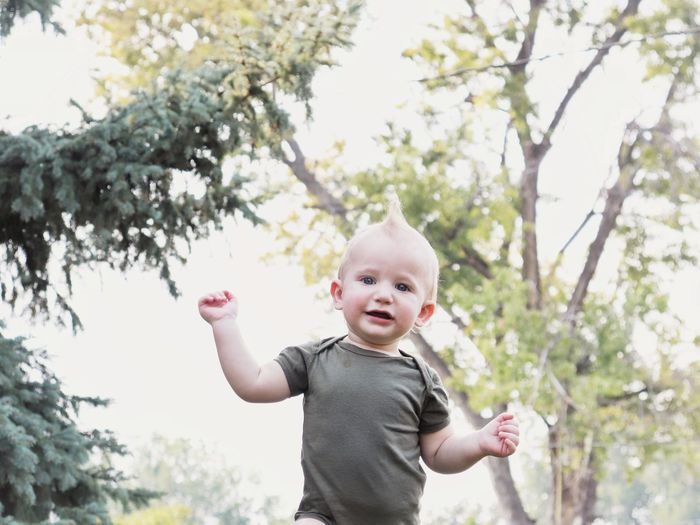 A small boy walks joyfully through the park with trees in the background