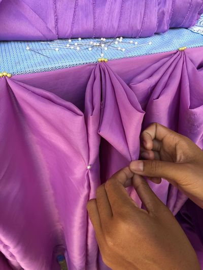 Close-up of hands making decoration with purple textile