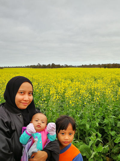 View over a blossoming rapeseed field in a rural landscape. Yellow Flowers Yellow Color Yellow Flower Yellow Fields Dark Blue Sky Blue Sky Rapeseed Blossom RapeFlowers Rapeseed Field Rapeseed Nature Land Plant Child Portrait Real People Childhood Family Beauty In Nature Looking At Camera Togetherness Field Women Lifestyles Sky Females Yellow Bonding Boys Innocence