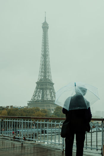 Rear view of man with umbrella against sky during rainy season