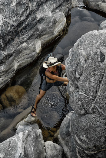 Am athletic woman in a cowboy hat climbs up out of a canyon in Burro Creek Wilderness Athletic Hat Jeans Sandals Woman Adventure Beauty In Nature Climbing Cowboy Hat Day Fitness Full Length Lifestyles Nature Outdoor Adventure Outdoors People Real People River Rock Climbing Rock Face Shorts Strong Water Waterfall