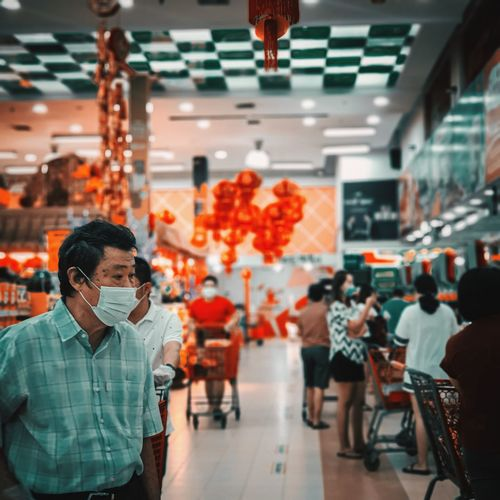 Man wearing mask looking away at shopping shopping mall