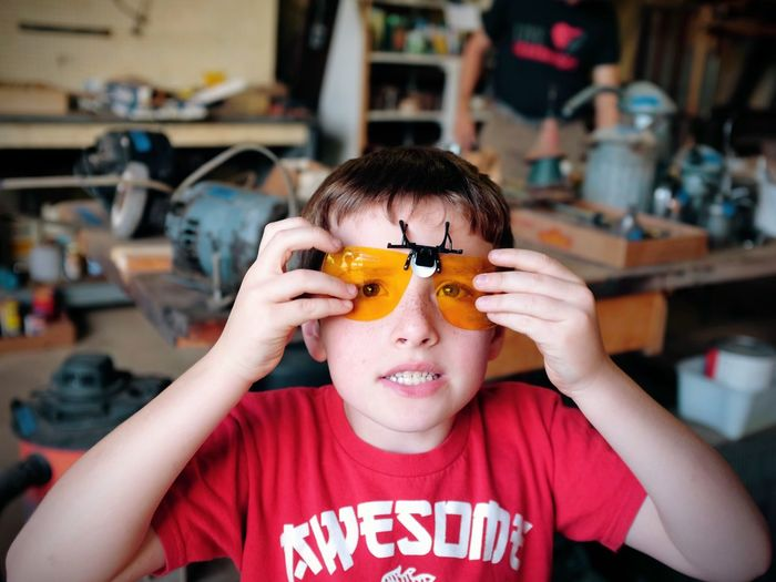 Portrait of boy wearing protective eyewear at garage