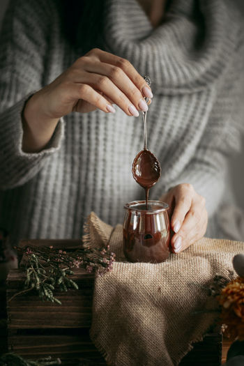 Midsection of woman holding spoon over chocolate jar on table