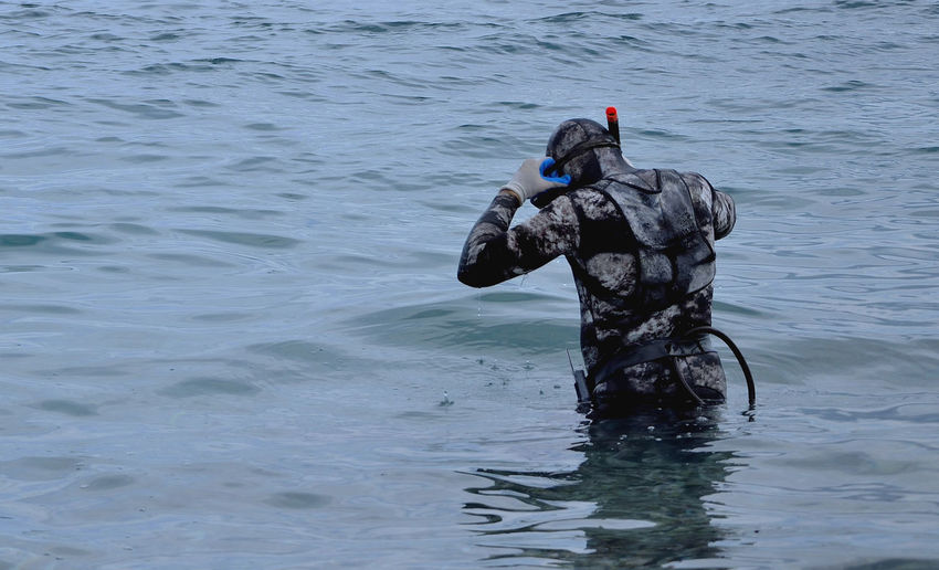 Rear view of diver standing in sea