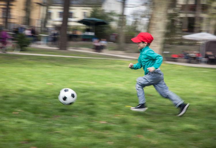 Full length of boy playing soccer ball
