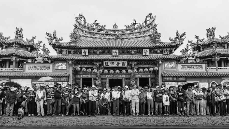 People in front of traditional building against sky