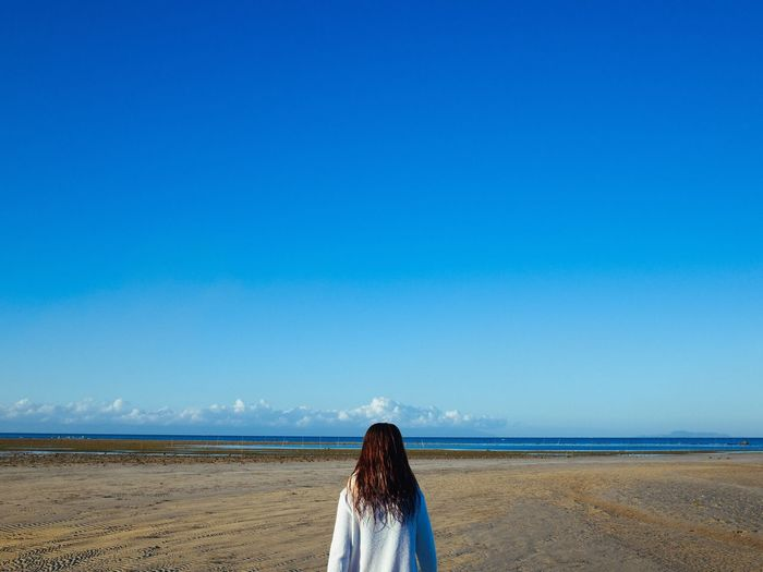 Rear view of woman standing on beach against clear blue sky