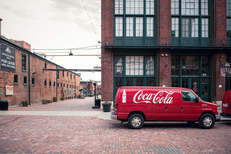 A red Coca Cola car in Canada. Ad Architecture Brick Building Building Exterior Built Structure Car City Coca Cola Communication Day Land Vehicle Mode Of Transportation Motor Vehicle No People Outdoors Red Safety Sign Street Text Transportation Urban Western Script The Street Photographer - 2018 EyeEm Awards The Architect - 2019 EyeEm Awards