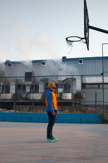 Full length of young man at basketball court against sky