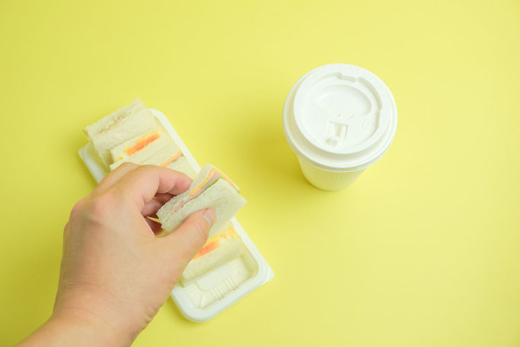 Coffee Lunch Meal Colored Background Drink Drinking Glass Finger Food Food And Drink Hand Holding Human Body Part Human Hand Indoors  Light Meal One Person Takeout Takeout Foods Yellow Yellow Background