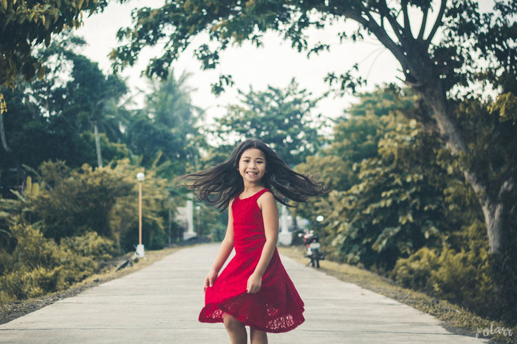 Portrait of beautiful young woman on road against trees