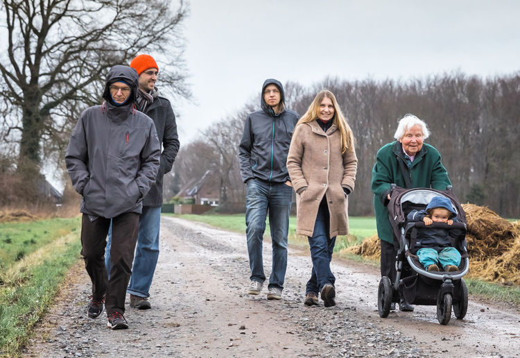 Multi-generation family in warm clothing walking on dirt road against sky