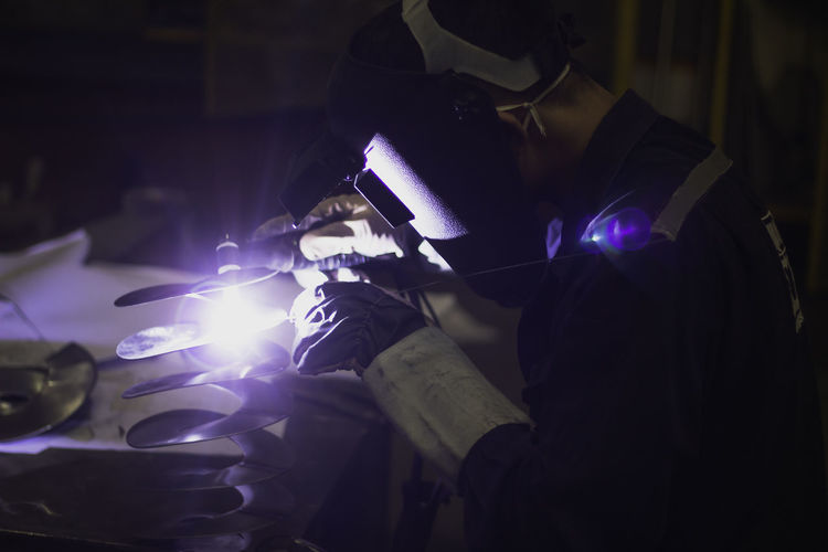 Side view of man welding at workshop