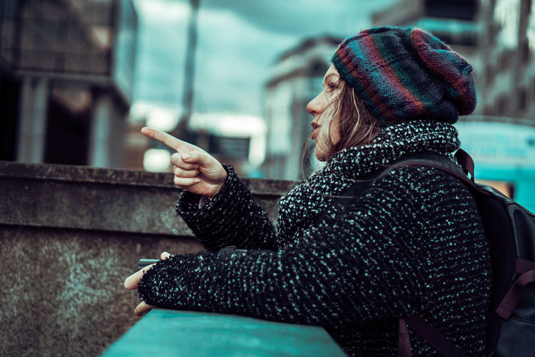 Woman in warm clothing pointing by retaining wall in city