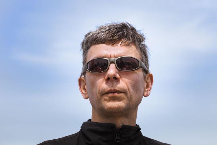 Portrait of senior man wearing sunglasses against sky