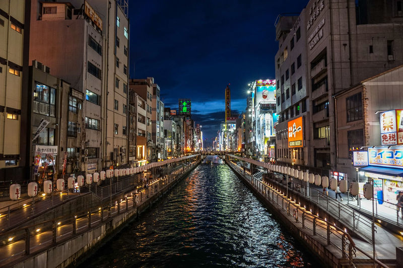 Canal amidst illuminated buildings in city at night