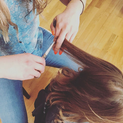 High angle view of hairdresser cutting hair of girl at salon