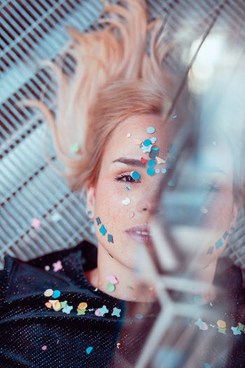 Portrait of woman with confetti on face lying on floor