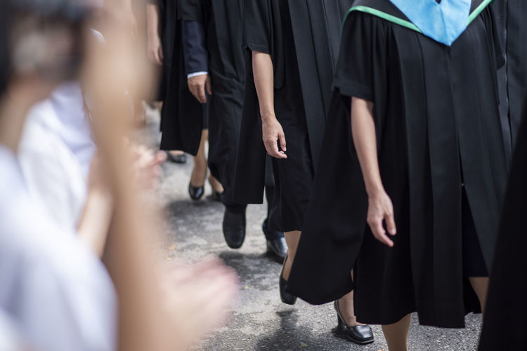 Midsection of people in graduation gown standing outdoors