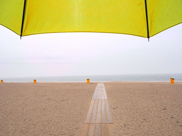 Cropped Image Of Yellow Wet Umbrella At Beach During Monsoon