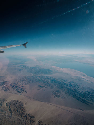 Aerial view of airplane wing over landscape against blue sky
