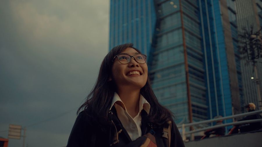 Smiling Young Woman Against Modern Building In City