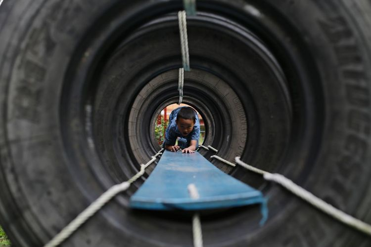 Boy playing in tunnel at playground