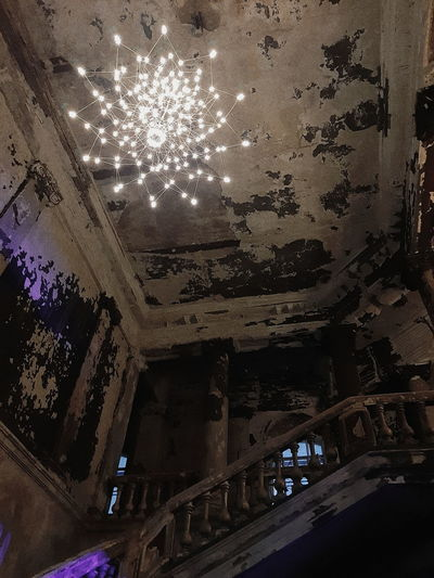 Low angle view of illuminated ceiling in abandoned building