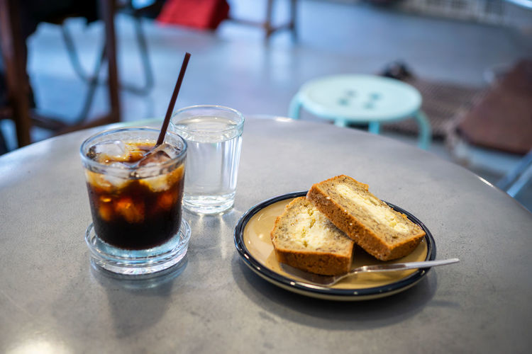 Black coffee and banana bread served in the afternoon at the famous coffee shop in Chiang Mai. Bread Breakfast Close-up Day Drink Drinking Glass Eating Utensil Focus On Foreground Food Food And Drink Freshness Glass Household Equipment Indoors  Meal No People Plate Ready-to-eat Refreshment Serving Size Still Life Table
