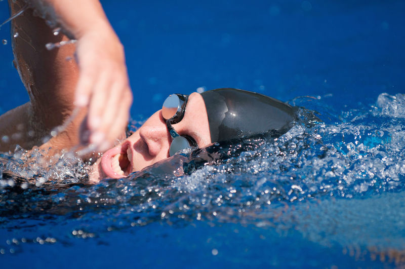 Swimmer Close-Up 20s Attractive Female Goggles Mouth Sunlight Swimming Swimming Cap Woman Young Action Black Blue Caucasian Female Lifestyles Outdoors Pool Professional Splash Sport Swimmer Swimming Pool Swimwear Water Wet