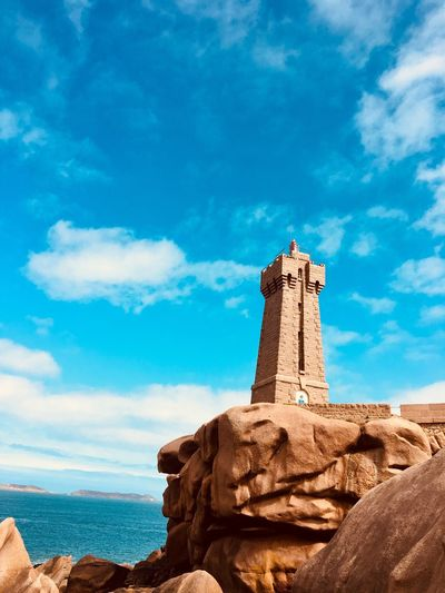 Lighthouse By Sea Against Cloudy Sky