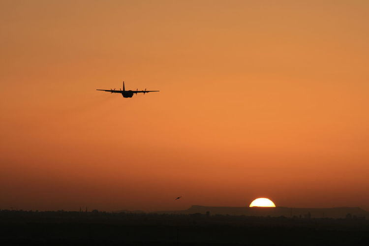Air Vehicle Airplane Beauty In Nature Copy Space Flying Mid-air Mode Of Transportation Motion Nature No People on the move Orange Color Outdoors Scenics - Nature Silhouette Sky Sun Sunset Transportation Travel