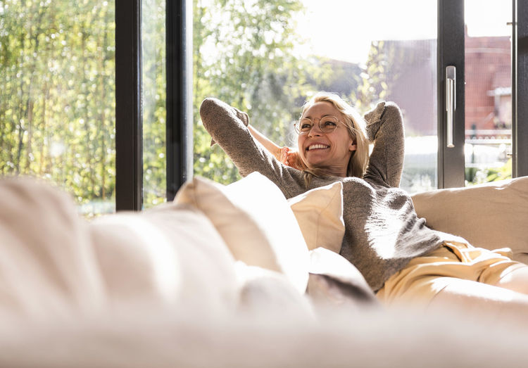 Portrait of smiling woman lying on window at home