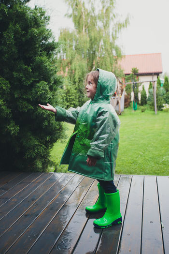 Full length of cute girl wearing raincoat and rubber boots while standing on wet floorboard during rainy season