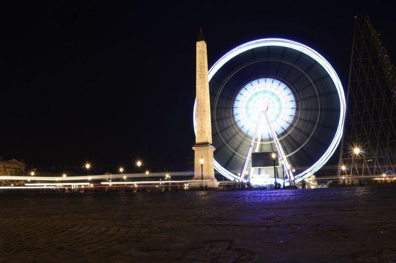 Illuminated roue de paris by obelisk of luxor at place de la concorde
