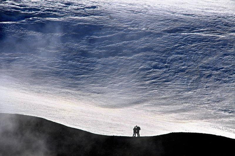 Two people standing on rocky terrain