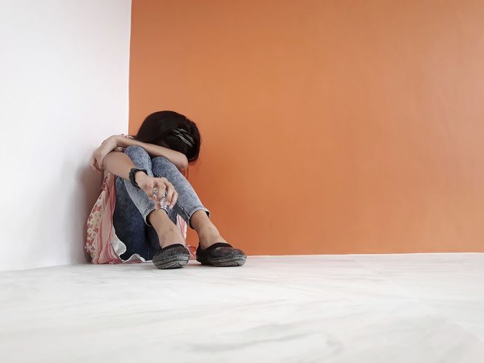 Depressed young woman sitting by wall