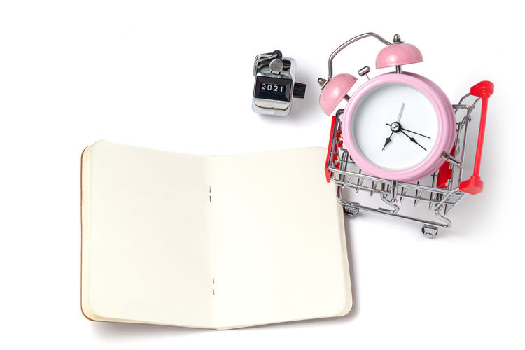 High angle view of clock on book against white background