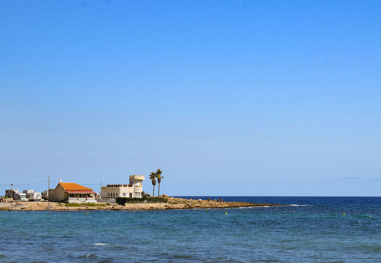 Mediterranean idyll Palm Trees Beach Life Beach Cottage Mediterranean Sea Water Sea Blue Clear Sky History Sky Architecture Building Exterior Built Structure View Into Land Calm Hut Shore Rippled Tranquil Scene Horizon Over Water Ocean Countryside