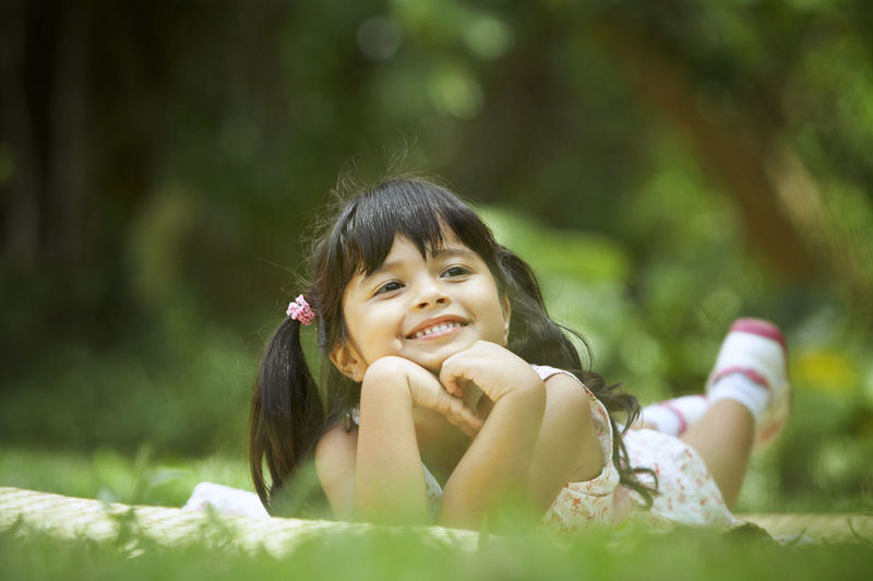 Portrait of smiling girl lying on field